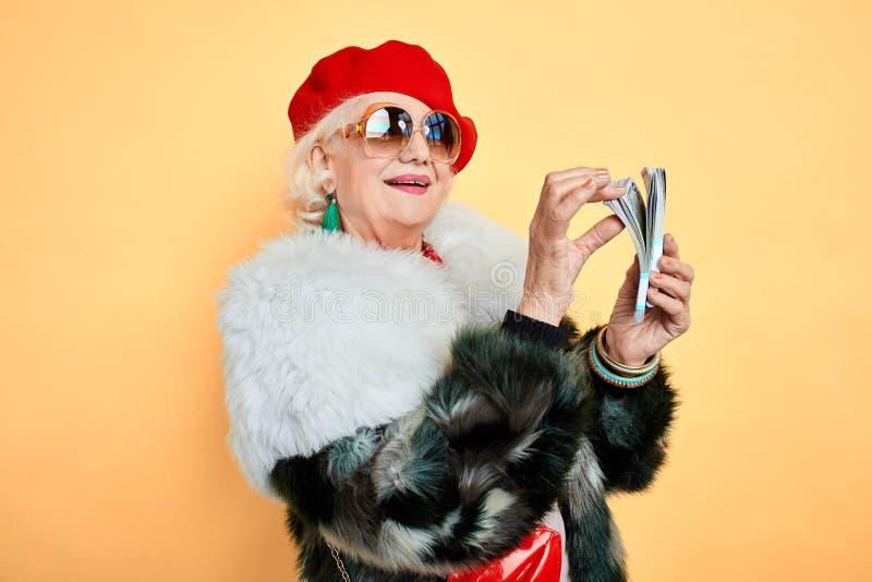 Grootmoeder die zich bij verdiend geld verheugen stock fotografie