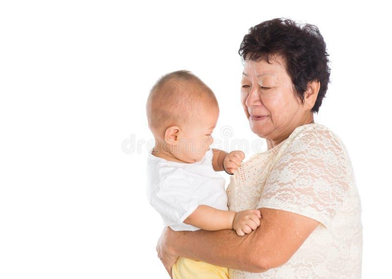 Grootmoeder die zorgkleinkind nemen stock afbeeldingen