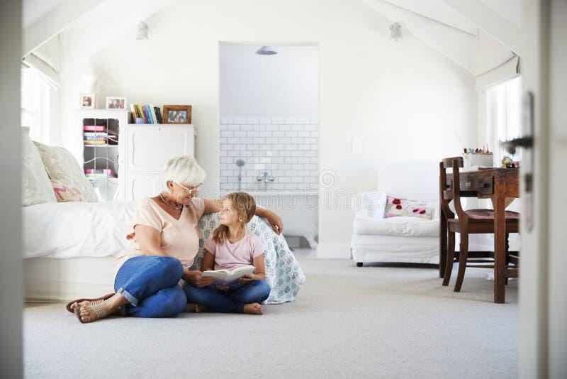 Grootmoeder en kleindochter die een boek in haar slaapkamer lezen stock afbeeldingen