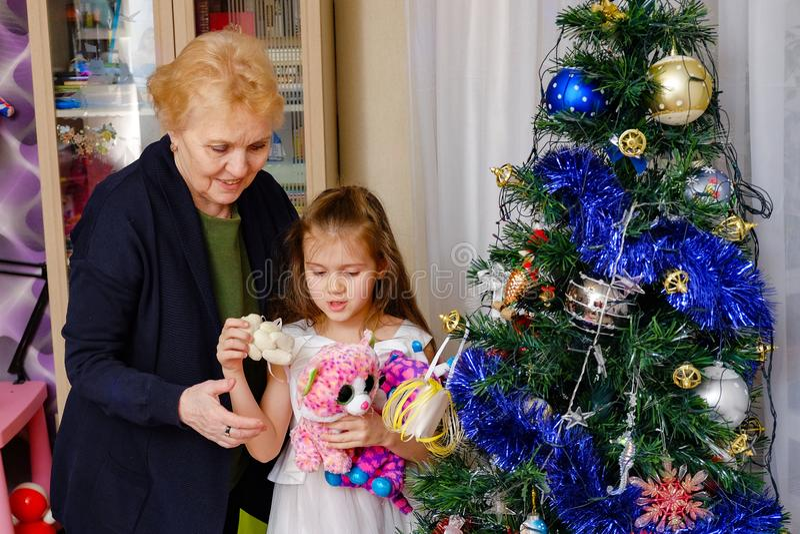 Grootmoeder en kleindochter die een Kerstboom verfraaien stock foto