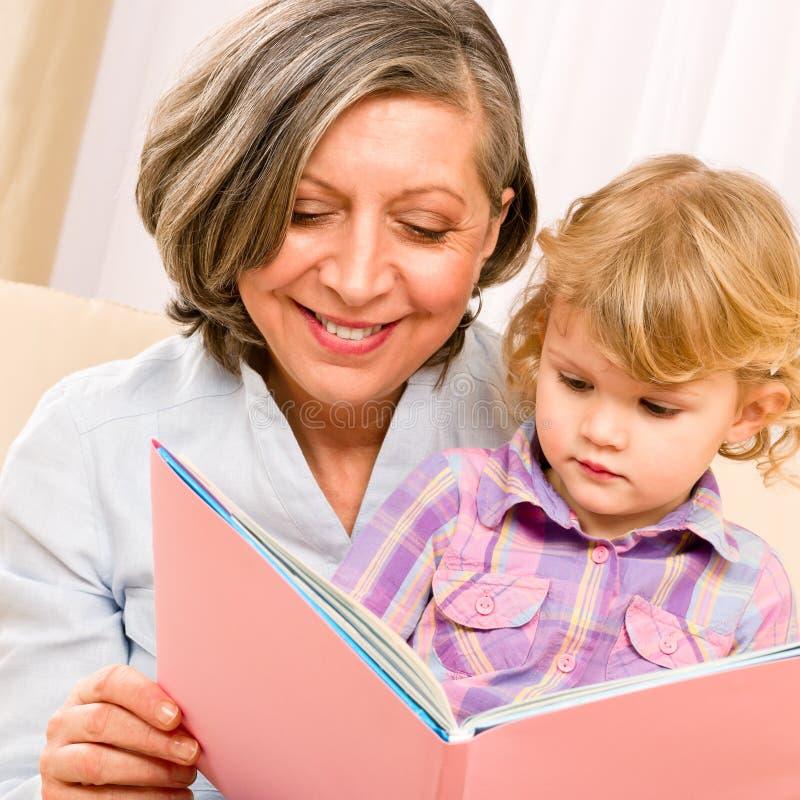Grootmoeder en kleindochter gelezen boek samen royalty-vrije stock afbeelding
