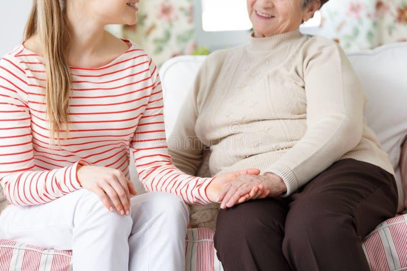 Grootmoeder en Kleindochterholdingshanden stock foto's