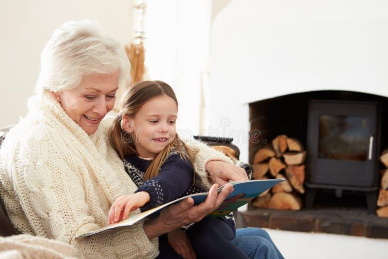 Grootmoeder en Kleindochterlezingsboek thuis samen royalty-vrije stock afbeelding