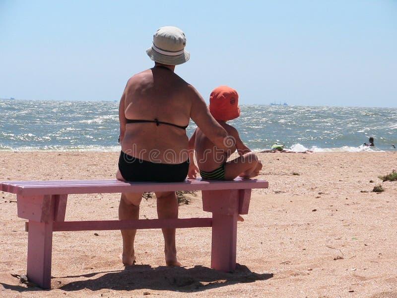 Grootmoeder en kleinkind op een strand stock afbeelding