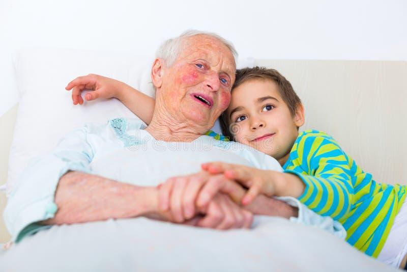Grootmoeder en kleinzoon in bed stock foto's