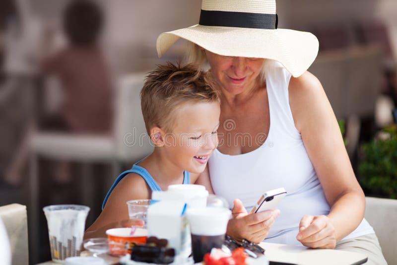 Grootmoeder en Kleinzoon die Celtelefoon samen met behulp van stock afbeeldingen