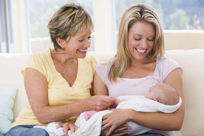 Grootmoeder en moeder in woonkamer met baby stock foto