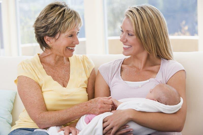 Grootmoeder en moeder in woonkamer met baby royalty-vrije stock afbeelding
