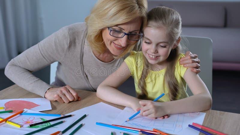 Grootmoeder het besteden tijd met kleindochter en het onderwijzen van haar die, familie schilderen stock foto