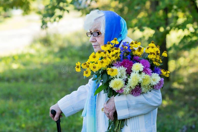 Grootmoeder met een riet en bloemen royalty-vrije stock foto