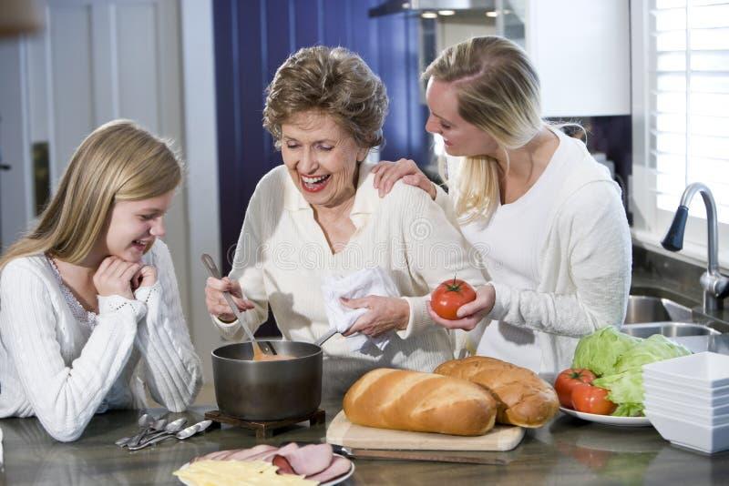 Grootmoeder met familie het koken in keuken stock fotografie