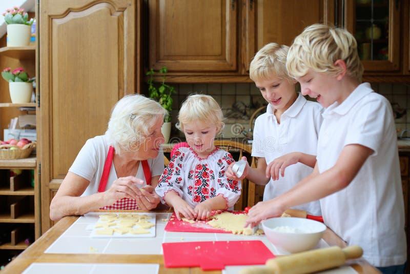Grootmoeder met grandkids die in de keuken koken royalty-vrije stock fotografie