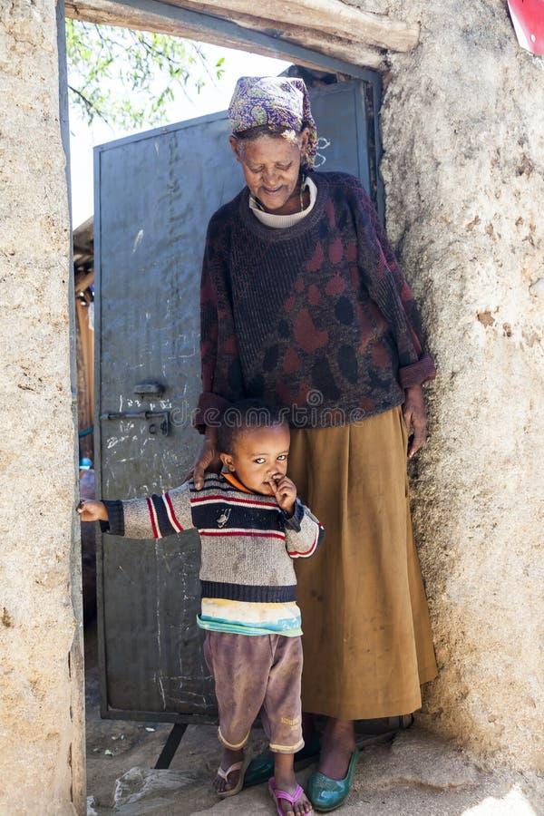 Grootmoeder met kleinkind het stellen in ingang van hun huis in stad van Jugol Harar ethiopië stock afbeelding