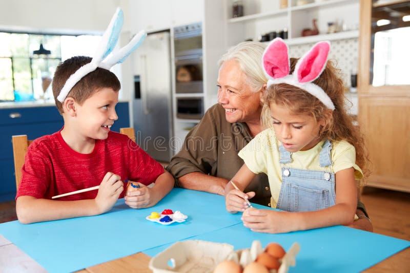 Grootmoeder met Kleinkinderen die Konijnoren dragen die Paaseieren thuis samen verfraaien royalty-vrije stock foto's