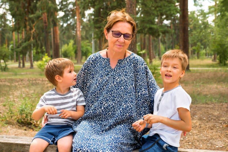 Grootmoeder met kleinzonen Gelukkig kinderjarenconcept De familie van meerdere generaties Peuterlevensstijl Glimlachende jongens  stock afbeeldingen