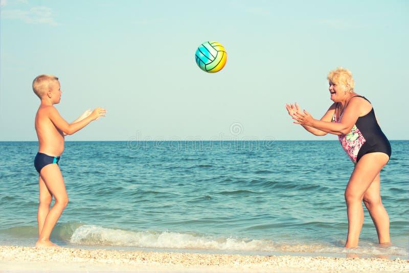 Grootmoeder met kleinzoon op strand het spelen bal stock fotografie