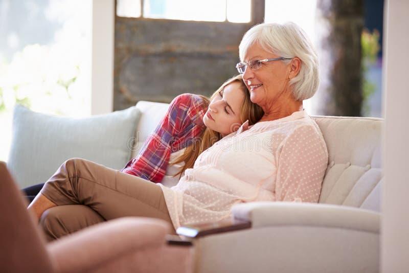 Grootmoeder met Volwassen Kleindochter die op TV op Bank letten royalty-vrije stock foto's
