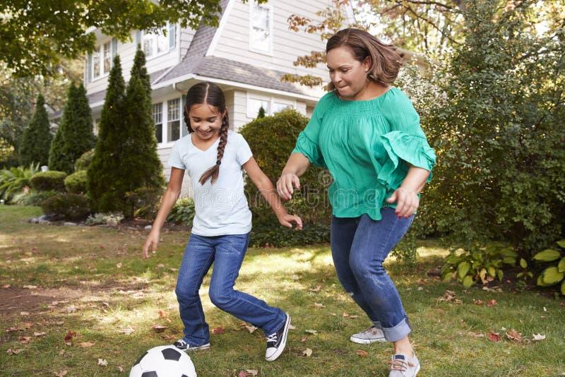 Grootmoeder Speelvoetbal in Tuin met Kleindochter royalty-vrije stock fotografie