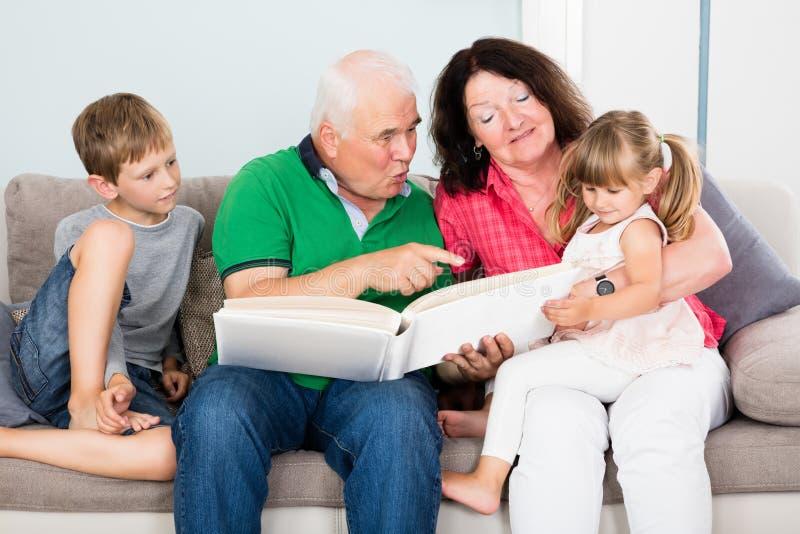 Grootouder en Kleinkinderen die Fotoalbum bekijken royalty-vrije stock afbeelding