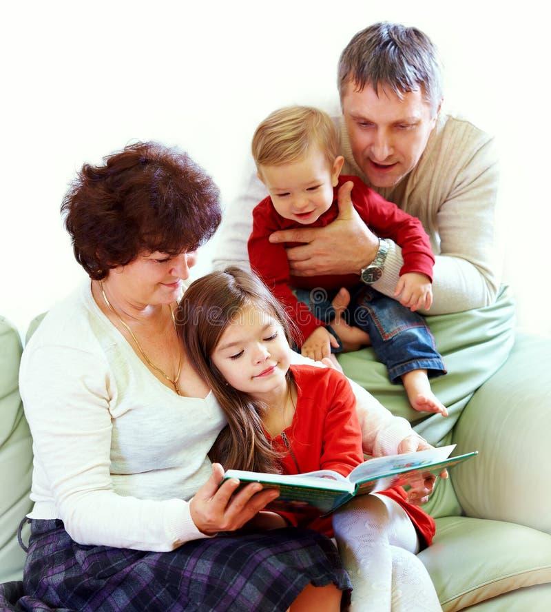 Grootouders die boeken lezen aan kleinkinderen stock foto