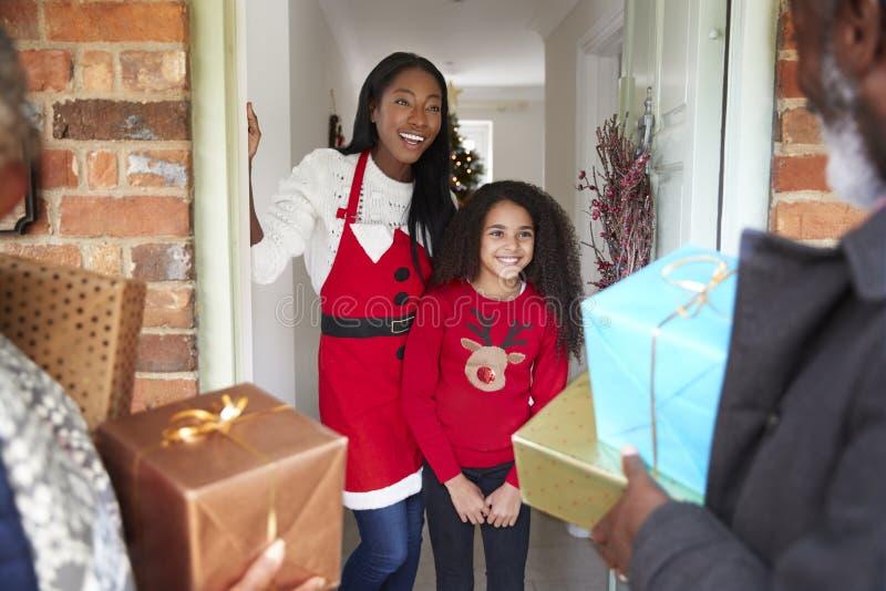 Grootouders die door Moeder en Dochter worden begroet aangezien zij voor Bezoek op Kerstmisdag met Giften aankomen stock foto