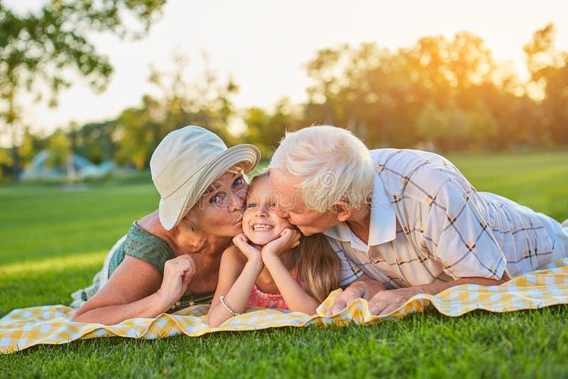 Grootouders die gelukkige kleindochter kussen royalty-vrije stock foto