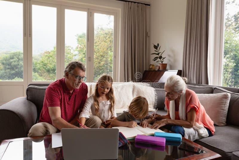 Grootouders die kleinkinderen met thuiswerk in woonkamer helpen bij comfortabel huis stock afbeeldingen