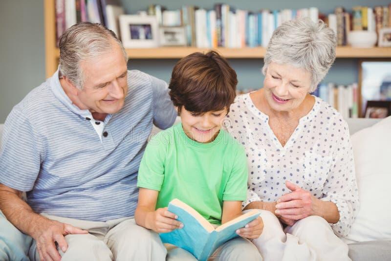 Grootouders die kleinzoon bijstaan terwijl het lezen van boek stock fotografie