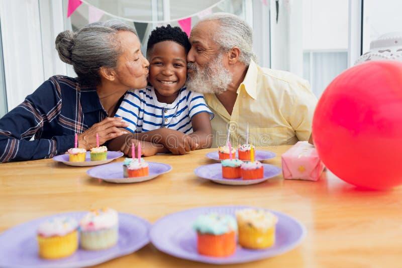 Grootouders die kleinzoon kussen stock afbeelding