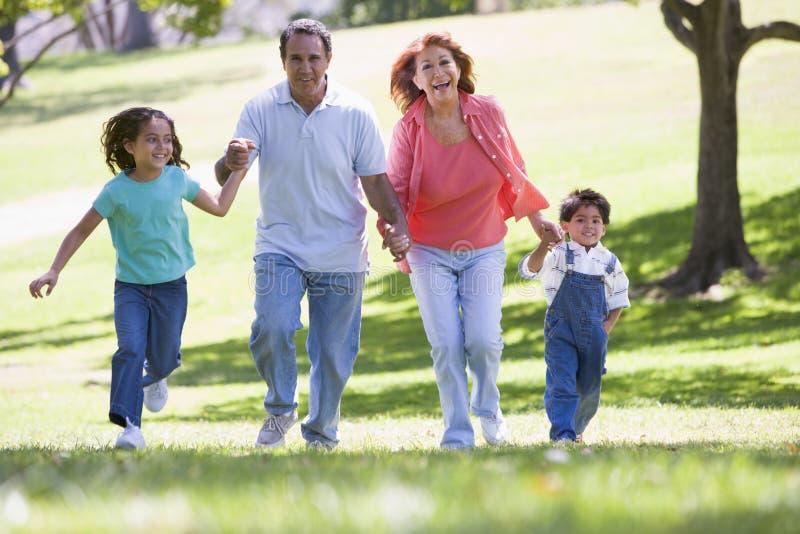 Grootouders die met kleinkinderen lopen stock foto's