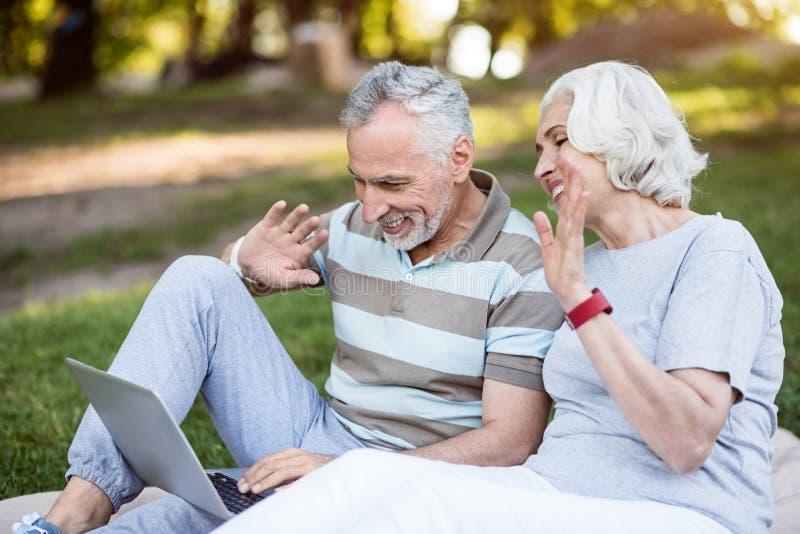 Grootouders die via skype met hun jonge degenen spreken stock afbeelding