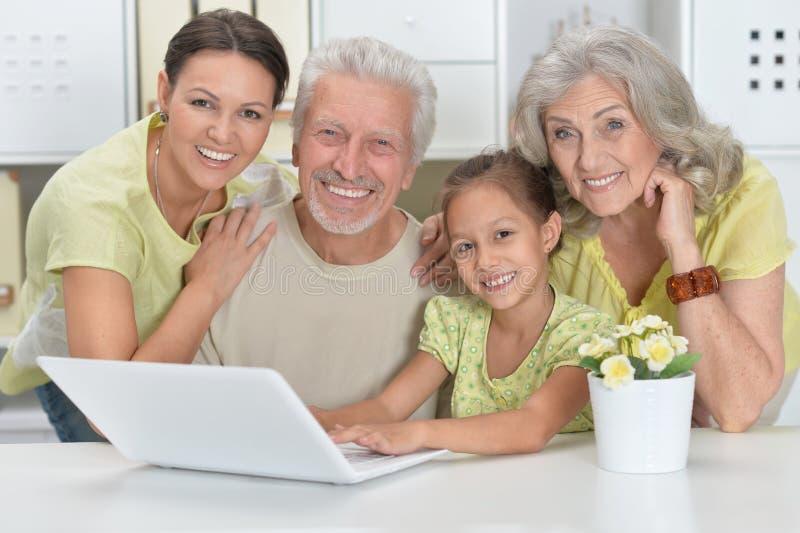 Grootouders, dochter en kleindochter die laptop met behulp van royalty-vrije stock foto's