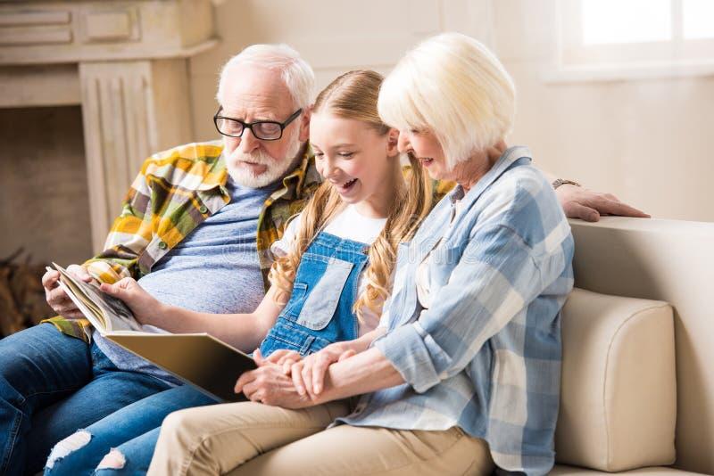 Grootouders en het glimlachen kleindochterzitting op bank en het bekijken fotoalbum stock afbeelding
