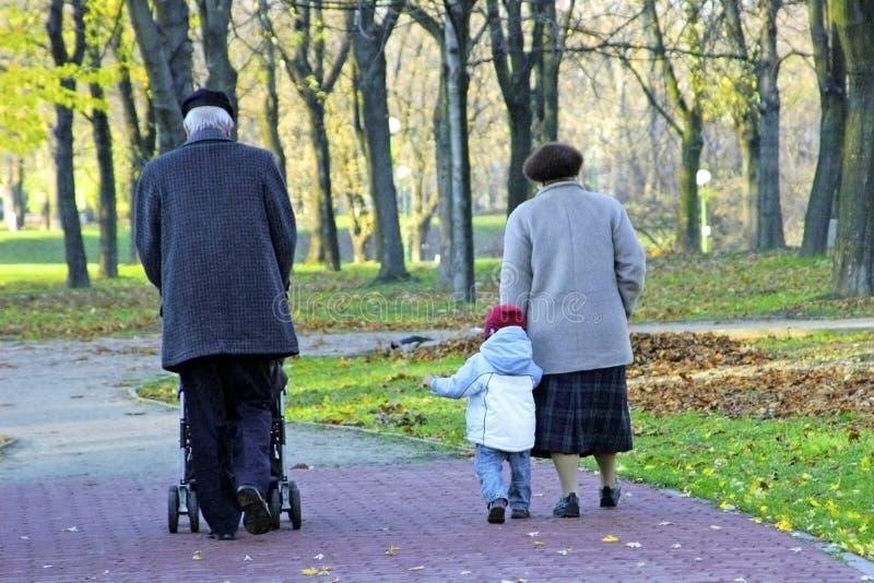 Grootouders en kleinkind die in het park lopen stock afbeelding