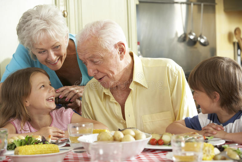 Grootouders en Kleinkinderen die Maaltijd samen in Keuken eten stock foto