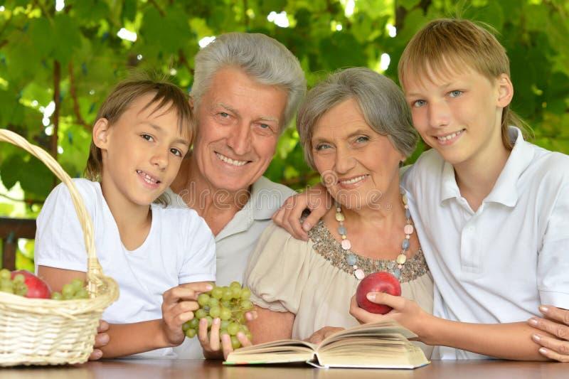 Grootouders en kleinzonen die bij lijst zitten stock foto