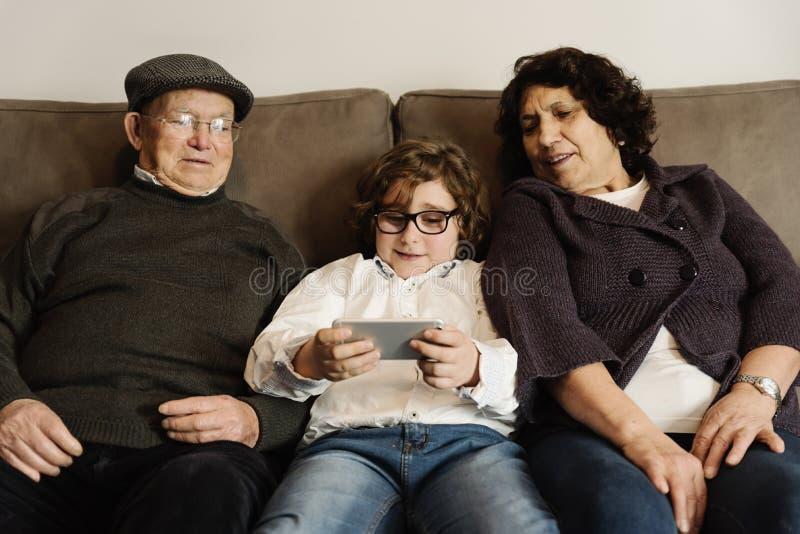 Grootouders en kleinzoon mobiel gebruiken stock afbeelding