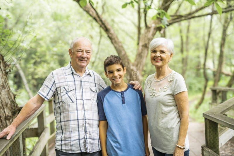 Grootouders met grandkid op de zomerbos die grote tijd hebben royalty-vrije stock afbeeldingen