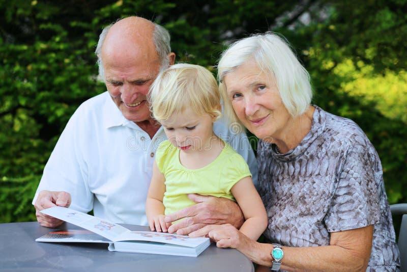 Grootouders met kleinkind het letten op fotoalbum royalty-vrije stock afbeeldingen