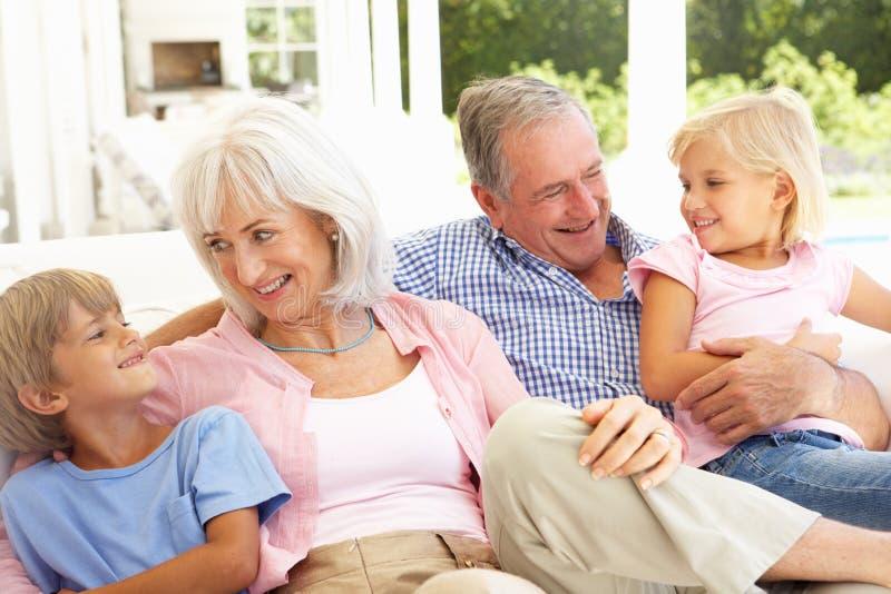 Grootouders met Kleinkinderen die samen ontspannen stock fotografie