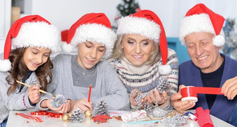 Grootouders met kleinkinderen die voor Kerstmis voorbereidingen treffen stock foto