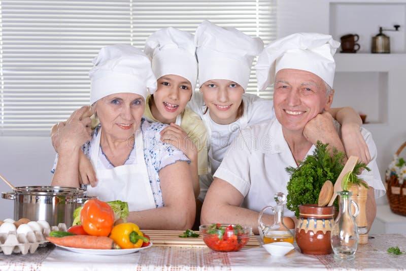 Grootouders met kleinzonen die samen koken stock foto's