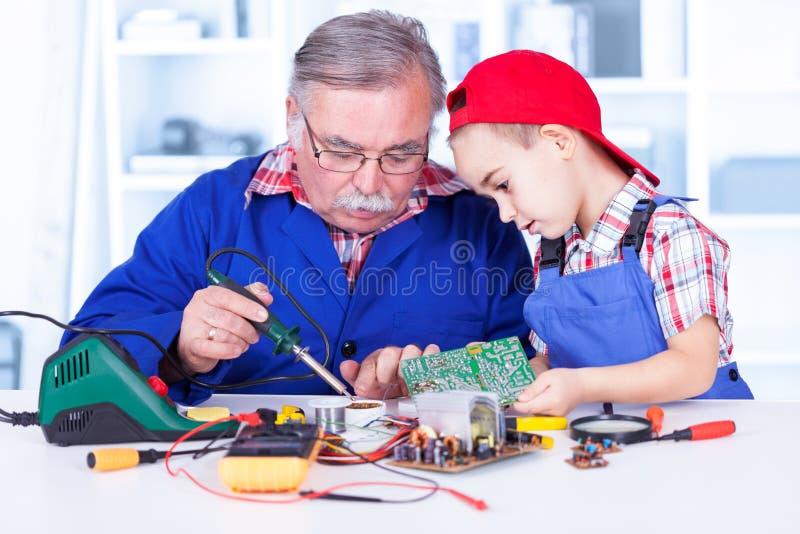 Grootvader die aan kleinkind verklaren hoe het solderen werkt royalty-vrije stock foto's