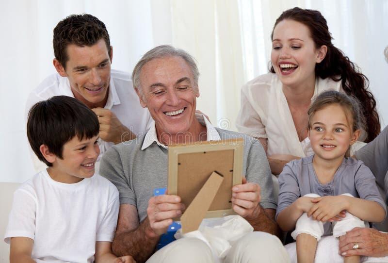 Grootvader die een foto met zijn familie bekijkt stock afbeelding