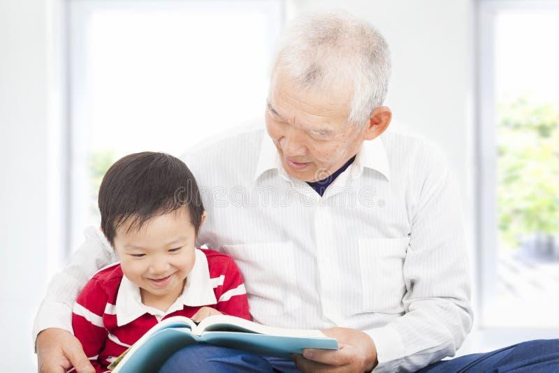Grootvader die een verhaalboek voor zijn kleinzoon lezen stock foto's