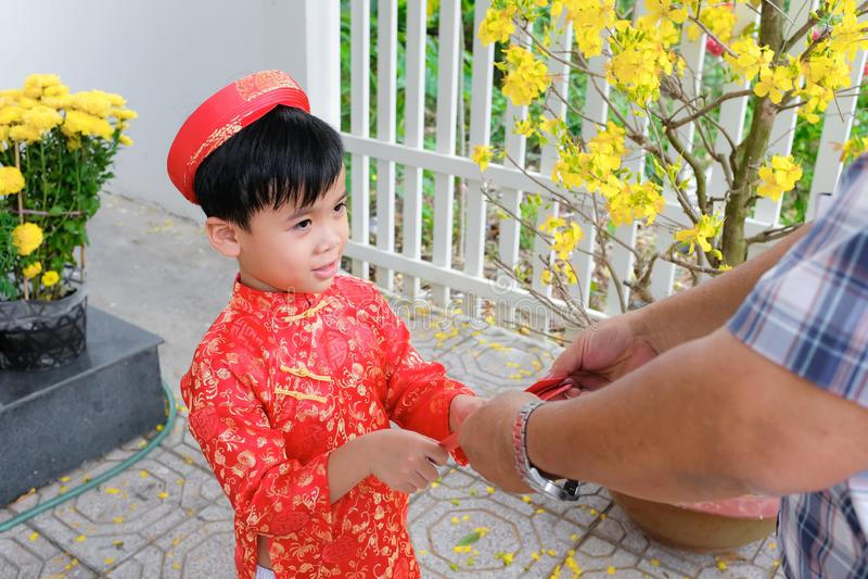 Grootvader die gelukkig geld geven aan kleinzoon op de eerste dag van Vietnamees maan nieuw jaar Tet stock fotografie