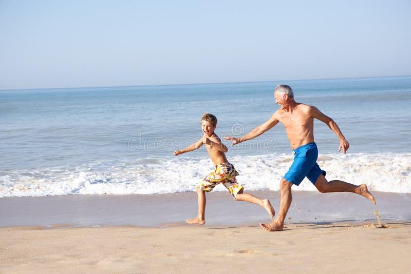 Grootvader die jonge jongen op strand achtervolgt royalty-vrije stock afbeeldingen