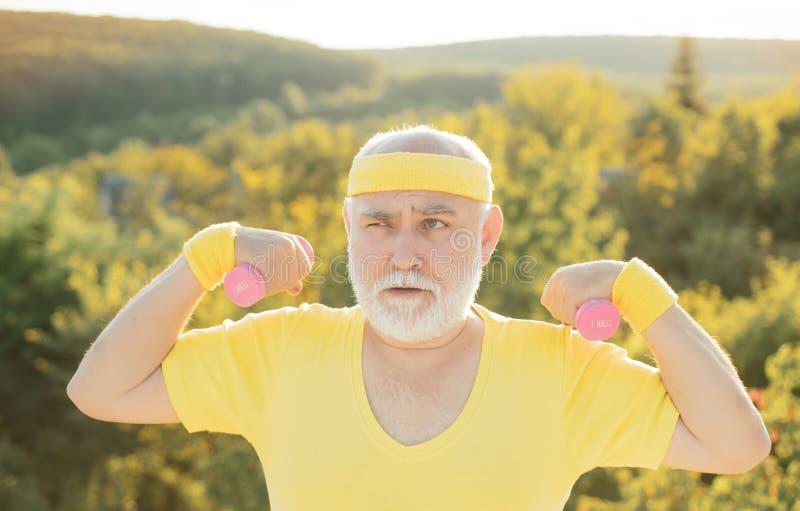 Grootvader die met domoor uitoefenen Sport voor de hogere mens Hogere mens die in park met gewichten uitwerken royalty-vrije stock fotografie