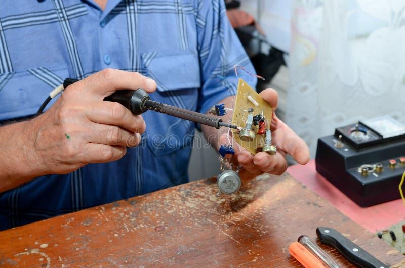 Grootvader die met een soldeerbout werken stock foto's
