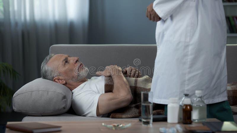 Grootvader die op laag en klagende arts van hartpijn liggen, gezondheidszorg royalty-vrije stock foto's